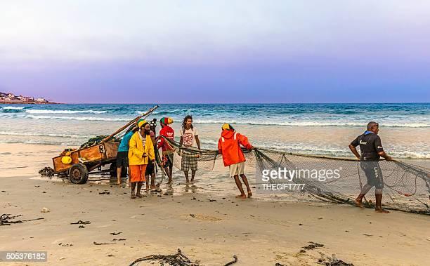 Pêcheur tirant dans les nets sur la plage