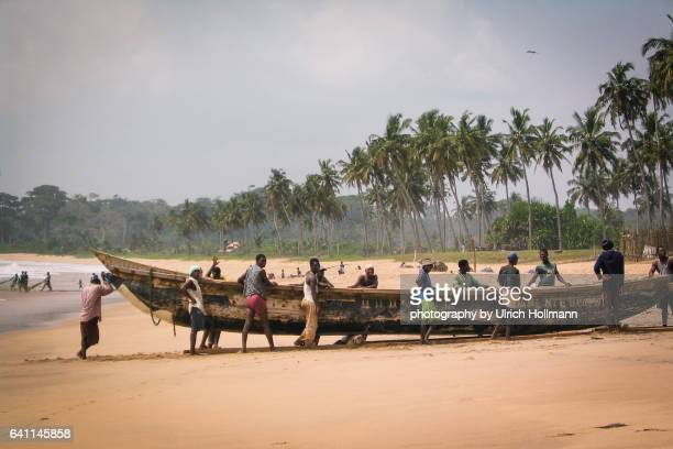 fishermen pulling in their boat, butre beach, ghana - fishing village stock pictures, royalty-free photos & images