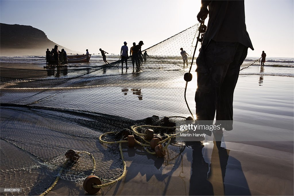 Fishermen pulling their catch onto the beach. : Bildbanksbilder
