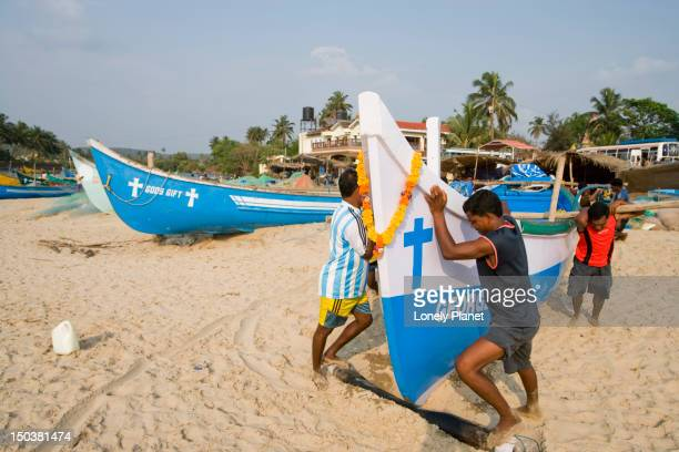 Fishermen pushing boat to the sea on the northern tip of Baga Beach.