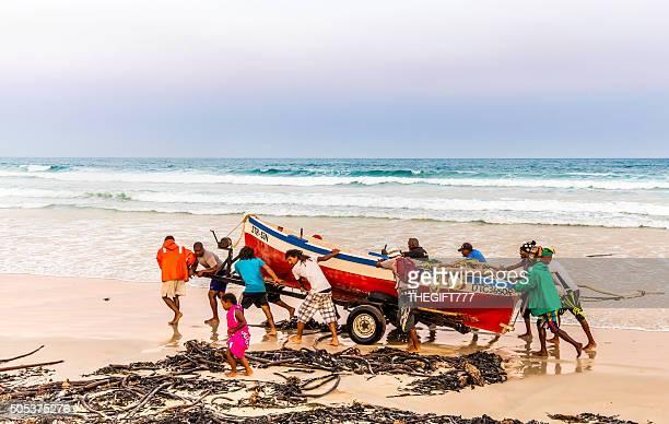 Fischer schieben Ihrem Boot am Strand