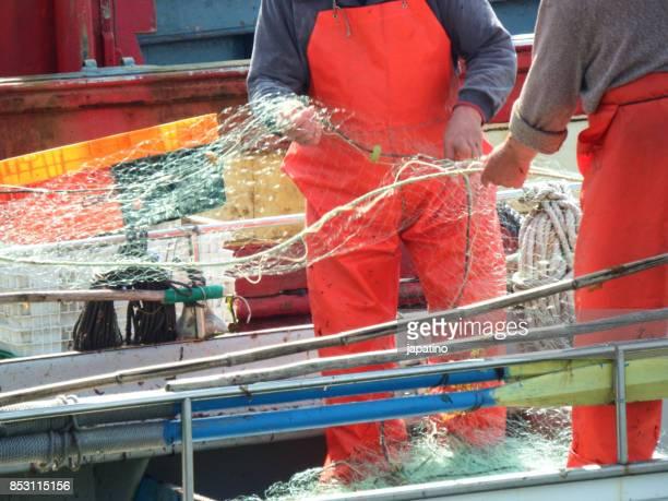 fishermen repairing fishing nets in the port of La Coruna