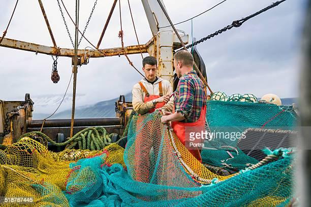 fishermen repairing net - fischer stock-fotos und bilder