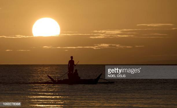 TOPSHOT Fishermen ride a powerboat during the sunset on the Philippine island of Boracay on October 25 2018 The Philippines reopens its crown jewel...