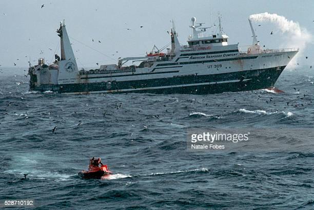 fishermen riding skiff to trawler at sea - bering sea stockfoto's en -beelden