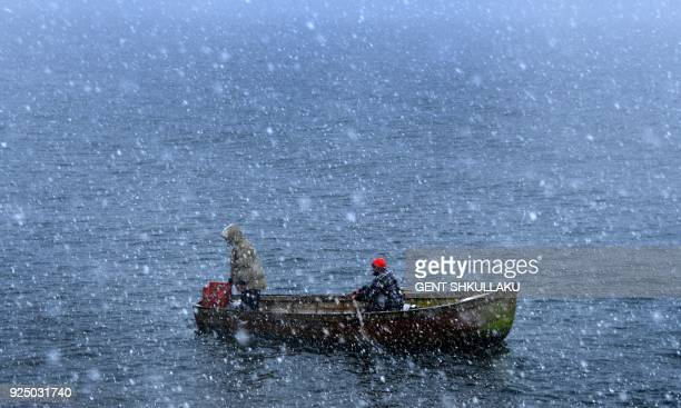 Fishermen row through heavy snowfall as they return to the shores of Ohrid Lake in Pogradec southeast Albania on February 27 2018 Heavy snow and low...
