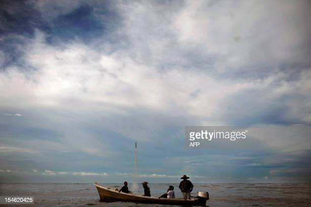 Fishermen sail a boat during a procession for Raphael the Archangel at the port of La Libertad 35 km south of San Salvador on October 23 2012 Saint...