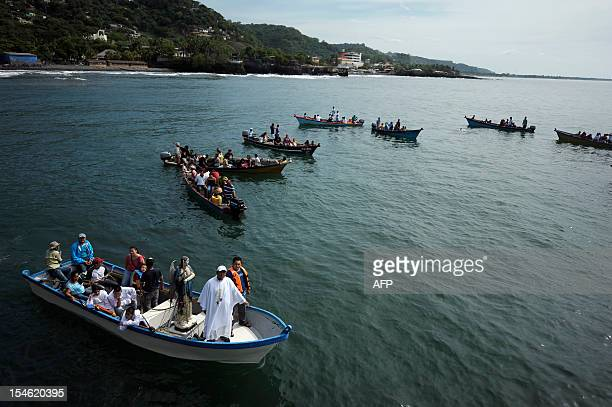 Fishermen sail a boat with an image of Saint Raphael the Archangel during a procession at the port of La Libertad 35 km south of San Salvador on...