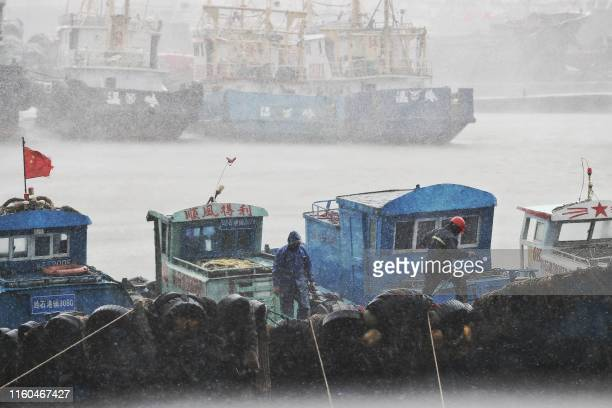 Fishermen secure boats at a port in Taizhou, China's eastern Zhejiang province, ahead of the arrival of Typhoon Lekima on August 9, 2019. - China...