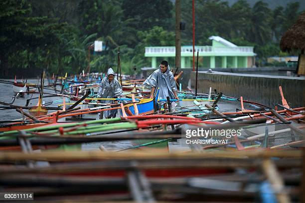 TOPSHOT Fishermen secure their boats in the bay of Santo Domingo Albay province on December 25 as typhoon NockTen approaches Babies toddlers and old...