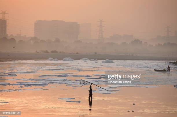 Fishermen seen at work in heavily polluted waters of the Yamuna River, at Kalindi Kunj on October 8, 2020 in New Delhi, India.