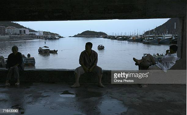 Fishermen sit down as boats lie tied up on the dock after Typhoon Saomai hit the Xiaguan Township on August 14 2006 in Cangnan County of Zhejiang...