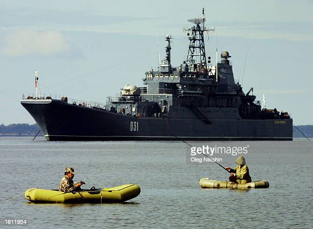 Fishermen sit in boats in the Divina river as a Russian warship passes August 31 2001 in Arkhangelsk Russia British World War II veterans who were...