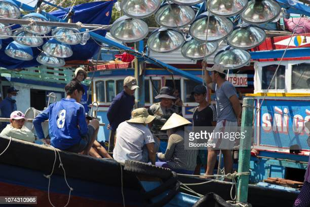 Fishermen sit on a boat during a tour hosted by Red Boat Fish Sauce off the island of Phu Quoc Vietnam on Thursday Nov 1 2018 Gourmands make...
