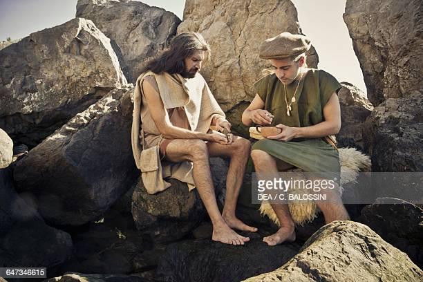 Fishermen sitting on rocks eating shellfish Illyrian civilisation mid3rd century BC Historical reenactment
