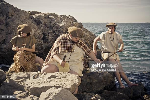 Fishermen sitting on rocks mending nets and fishing Illyrian civilisation mid3rd century BC Historical reenactment