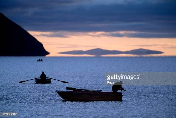 Fishermen stand on boats by the Amur River's mouth in the Okhotsk Sea October 1997 in Russian Federation.