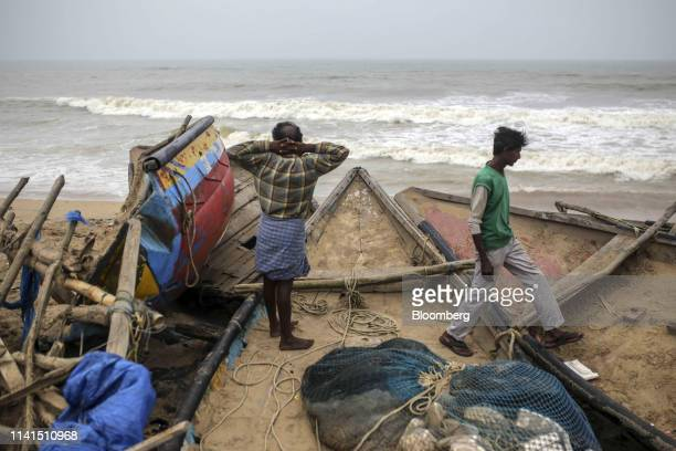 Fishermen stand on damaged fishing boats on a beach in the fishing village of Konark Odisha India on Sunday May 5 2019 Authorities launched a massive...