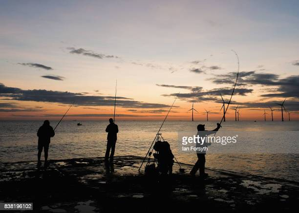 Fishermen stand on the end of the breakwater as they fish at South Gare on August 24 2017 in Redcar England The manmade breakwater at South Gare...