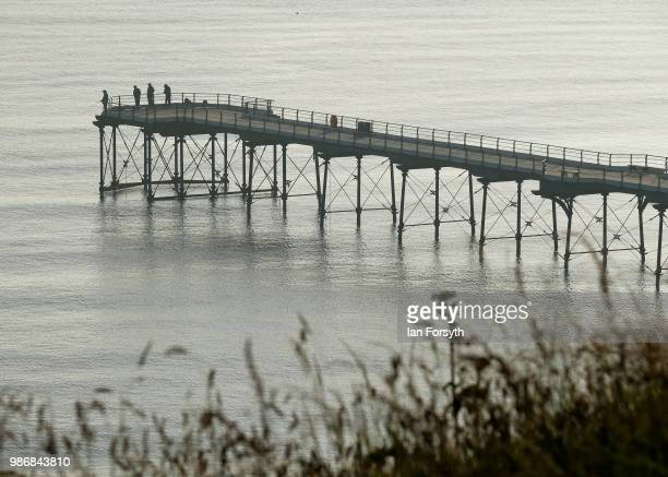 Fishermen stand on the end of the pier as sea fog shrouds the coast on June 29 2018 in SaltburnByTheSea England Low cloud and sea fog will cover many...