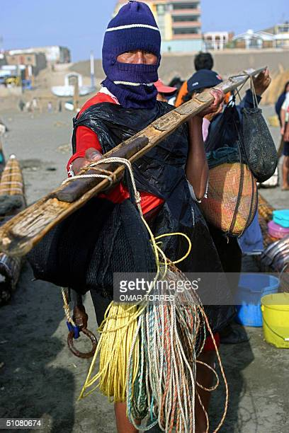 A fishermen still attired himself with his working gear shows the paddle he uses on his Caballito de Totora after arriving to the beach of Pimentel...