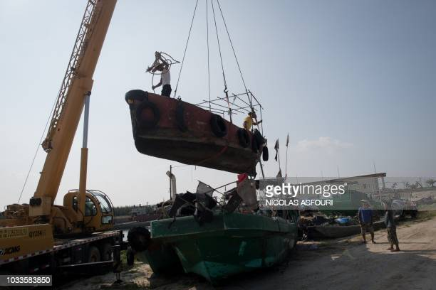 Fishermen take their boat of the water with a crane ahead of the arrival of the Super Typhoon Mangkhut in Sanhe village on the outskirts of Zhanjiang...