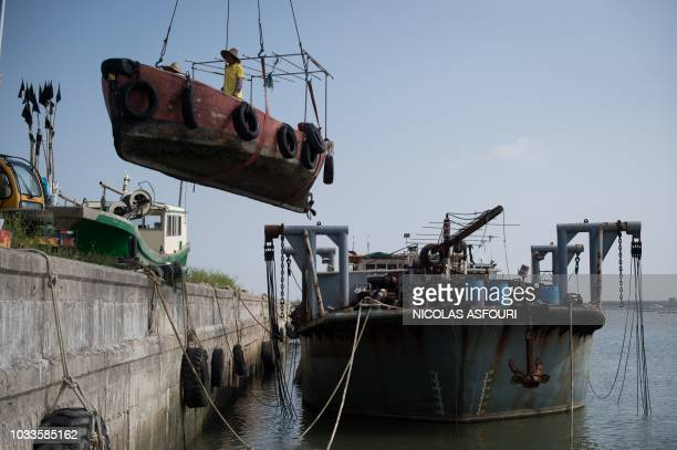 TOPSHOT Fishermen take their boat of the water with a crane ahead of the arrival of the Super Typhoon Mangkhut in Sanhe village on the outskirts of...