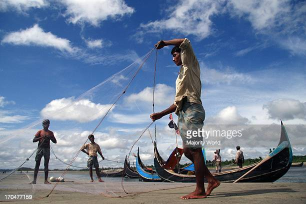 Fishermen takecare their fishing net after return from fishing Inani Beach Cox's Bazar Bangladesh June 07 2008