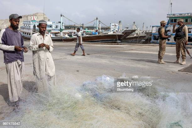 Fishermen tend to a fishing net as members of the security forces stand by at the harbor in Gwadar Balochistan Pakistan on Tuesday July 4 2018 What...