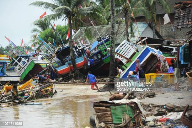 Fishermen tend to their traditional fishing boats which were damaged after being hit by a tsunami in the Teluk village, Labuan subdistrict in Banten...