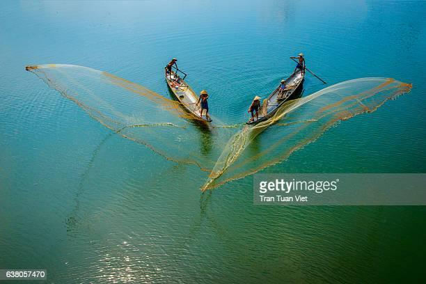 Fishermen throw fishing net on boats to catch fish in Hue, Vietnam.