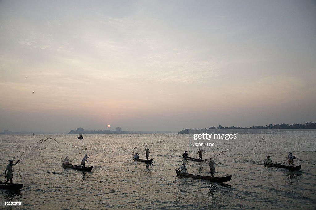 Fishermen throwing fishing nets in Cochin, India : Stock Photo