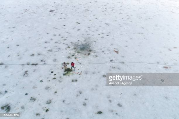 Fishermen try to fish over the frozen 'Lake Van' as it has been frozen due to extreme cold weather during winter season in Van Turkey on December 29...