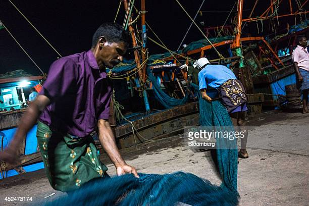 Fishermen unload a fishing net from a boat on the quayside in Puducherry India on Saturday July 19 2014 Indias gross domestic product growth forecast...
