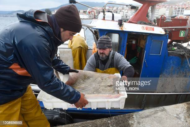 Fishermen unload the day's catch in the port of Bueu, northwestern Spain, on April 2, 2020. - Spain imposed a nationwide lockdown on March 14 to...