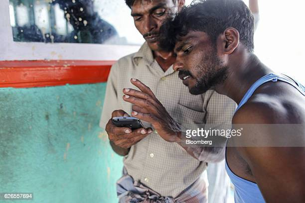 Fishermen use a smartphone on a fishing boat docked at the Nagor fishing harbor in Nagapattinam India on Saturday Oct 15 2016 Thousands of fishermen...