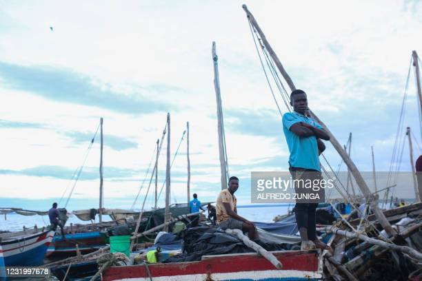 Fishermen wait at theor boats at the port of Paquitequete near Pemba on March 29, 2021. Sailing boats are expected to arrive with people displaced...