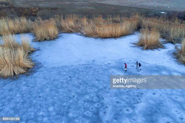Fishermen walk on the the frozen 'Lake Van' for fishing as the lake has been frozen due to extreme cold weather during winter season in Van Turkey on...