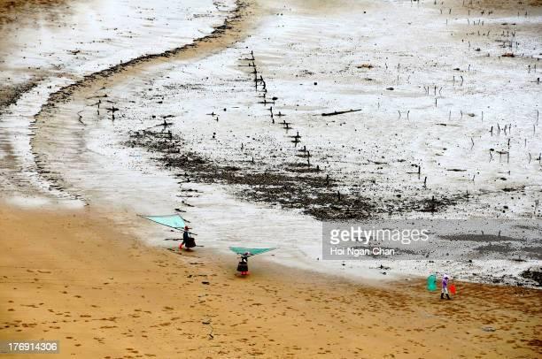 Fishermen walking on artistic Mudflats beach in Xiapu, Fujian, China.