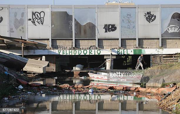 A fishermen walks beneath a 'sound barrier' attached along a stretch of the main highway which links Rio's international airport to the city center...