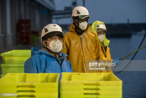 Fishermen wearing face masks and protective gear, look on as they wait for unloading the day's catch of anchovies on April 22, 2020 in Hondarribia,...