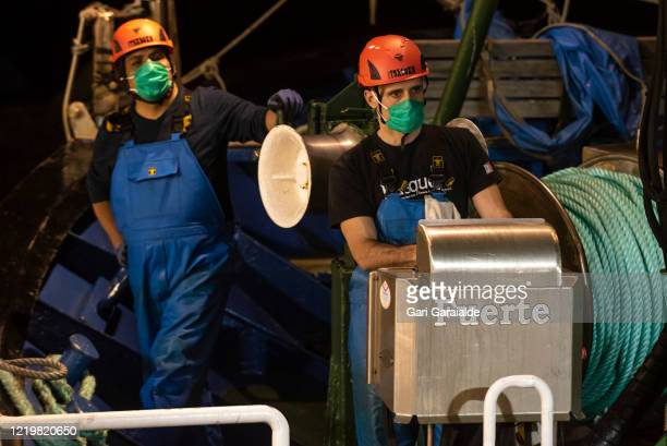 Fishermen wearing protective face masks finalize preparations to go fishing in the first anchovy campaign of the season on April 20, 2020 in...