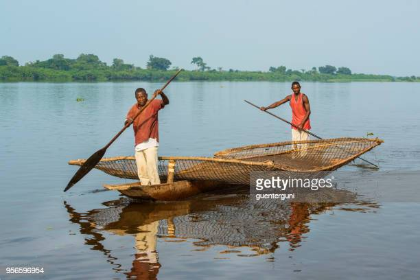 fishermen with a typical braided fishing net, congo river - dugout canoe stock photos and pictures