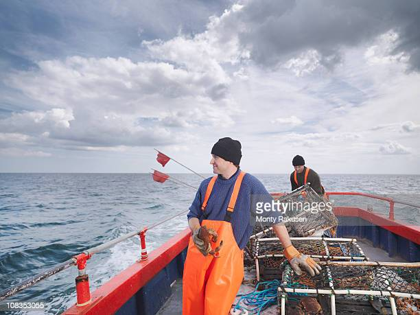 fishermen with crab and lobster pots - crab stock photos and pictures