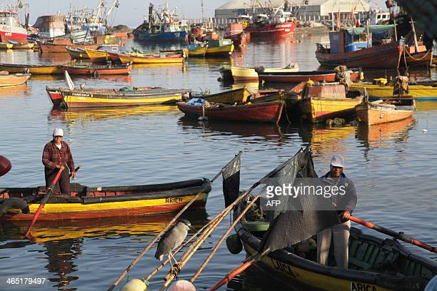 Fishermen work at the port of Arica Chile close to the border with Peru and about 2100 km north of Santiago on January 262014 Both Peruvians and...