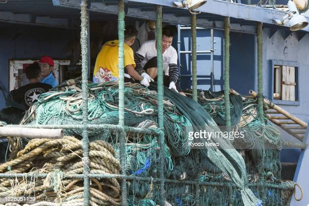 Fishermen work on a vessel docked at a port in Shishi in Fujian Provence in China on Aug 15 ahead of departure
