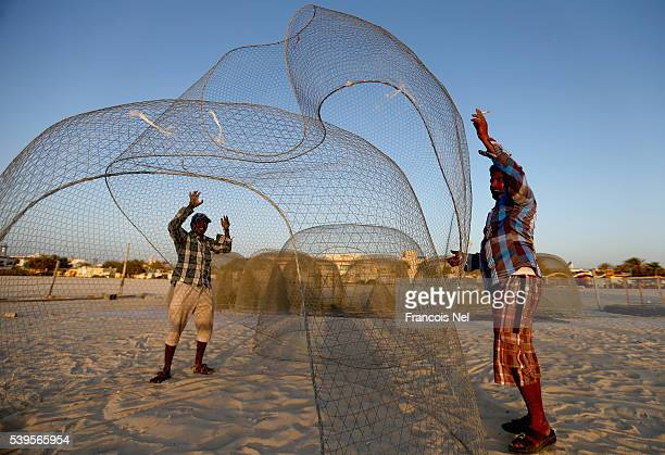 Fishermen work on traditional wire fishing baskets at Jumeirah Beach on June 12 2016 in Dubai United Arab Emirates