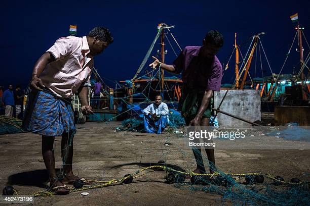 Fishermen work to untangle a fishing net on the quayside in Puducherry India on Saturday July 19 2014 Indias gross domestic product growth forecast...