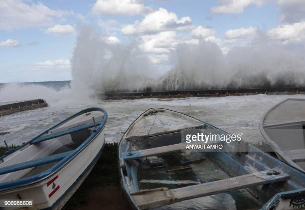 Fishermen's boats are lined up on the shore as waves crash against the seafront in Beirut amid heavy winds and rain that whipped across Lebanon on...