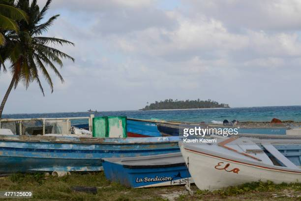 Fishermen's boats lie next to a palm tree on the beachfront against the Johnny Cay coral islet on January 24 2014 in San Andres Colombia Colombia has...